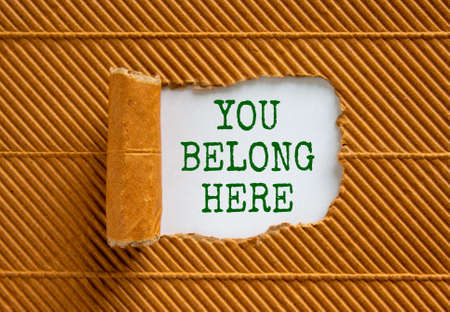 You belong here symbol. Words 'You belong here' appearing behind torn brown paper. Beautiful brown background. Business, diversity, inclusion, belonging and you belong here concept, copy space.
