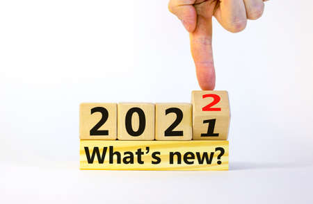 Business and 2022 new year concept. Businessman turns wooden cube with words '2022, 2021, what is new'. Black alarm clock and plant. Beautiful white background, copy space. 2022 what is new symbol. Standard-Bild