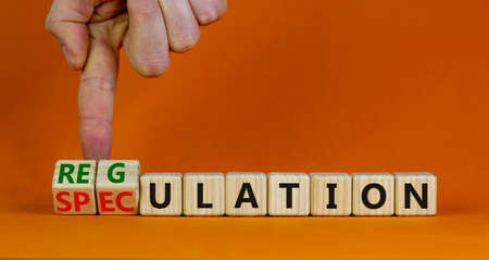 Speculation or regulation symbol. Businessman turns wooden cubes, changes the word speculation to regulation. Beautiful orange background, copy space. Business, speculation or regulation concept.