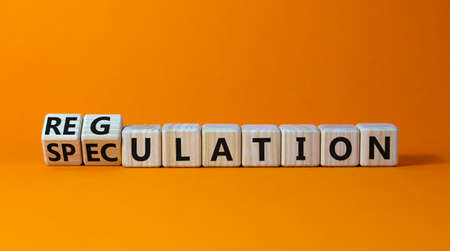 Speculation or regulation symbol. Turned cubes and changed the word speculation to regulation. Beautiful orange table, orange background, copy space. Business, speculation or regulation concept.