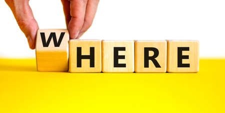 Where or here symbol. Businessman turns a wooden cube, changes the word 'where' to 'here'. Beautiful yellow table, white background, copy space. Business, where or here concept.
