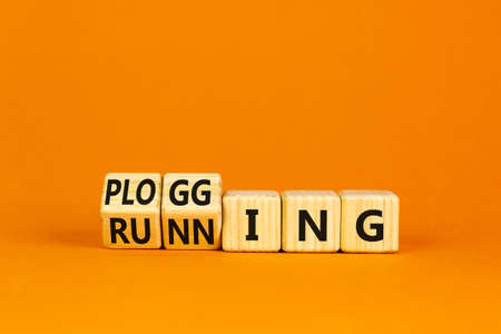 Running or plogging symbol. Turned wooden cubes and changed the word running to plogging. Beautiful orange table, orange background, copy space. Sports, ecological, running or plogging concept. 스톡 콘텐츠