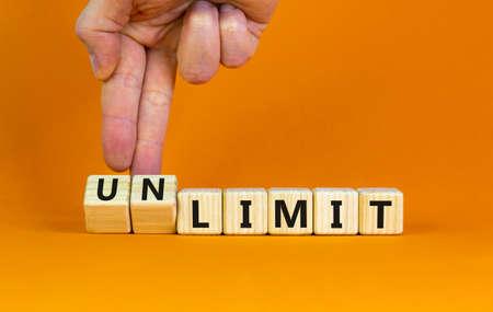 Limit or unlimit symbol. Businessman turns cubes, changes words 'limit' to 'unlimit'. Beautiful orange table, orange background, copy space. Business, limit or unlimit concept. 스톡 콘텐츠