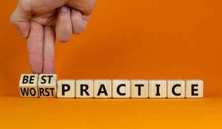 Best or worst practice symbol. Businessman turns wooden cubes and changes words 'worst practice' to 'best practice'. Beautiful orange background. Business, best or worst practice concept. Copy space. 스톡 콘텐츠