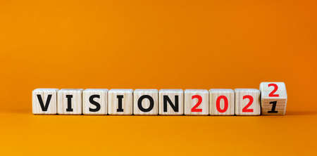 2022 vision new year symbol. Turned a wooden cube and changed words 'vision 2021' to 'vision 2022'. Beautiful orange background, copy space. Business, 2022 vision new year concept.
