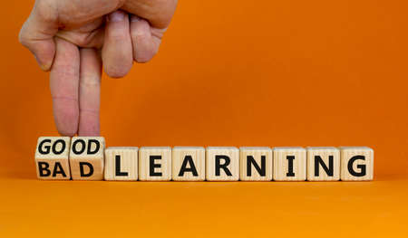 Good or bad learning symbol. Businessman turns cubes, changes words 'bad learning' to 'good learning'. Beautiful orange background. Business, education and good or bad learning concept. Copy space. 스톡 콘텐츠