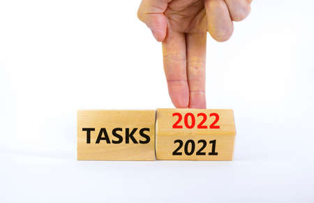2022 tasks new year symbol. Businessman turns a wooden cube and changes words 'Tasks 2021' to 'Tasks 2022'. Beautiful white background, copy space. Business, 2022 tasks new year concept.