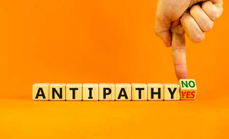 Antipathy yes or no symbol. Psychologist turns a wooden cube and change words 'antipathy no' to 'antipathy yes'. Beautiful orange background. Business and antipathy yes or no concept, copy space.