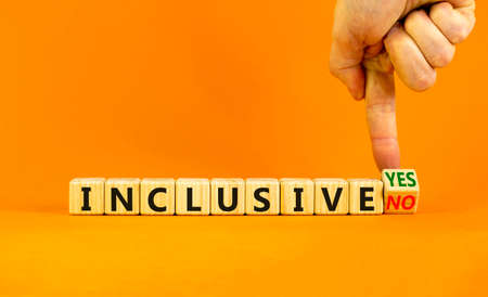 Inclusive yes or no symbol. Businessman turns a wooden cube and change words 'inclusive no' to 'inclusive yes'. Beautiful orange background. Business and inclusive yes or no concept, copy space.
