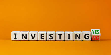 Investing yes or no symbol. Turned a wooden cube and changed words 'investing no' to 'investing yes'. Beautiful orange background. Business and investing yes or no concept, copy space.