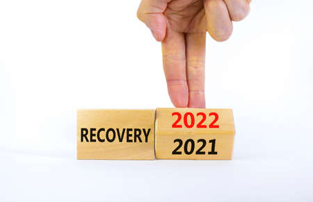 2022 recovery new year symbol. Businessman turns a wooden cube and changes words 'Recovery 2021' to 'Recovery 2022'. Beautiful white background, copy space. Business, 2022 recovery new year concept. 스톡 콘텐츠