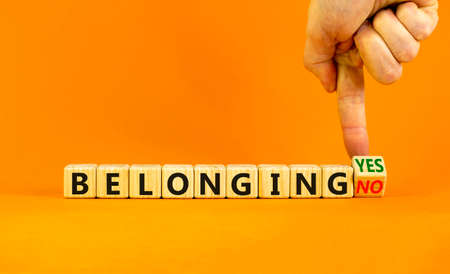 Belonging yes or no symbol. Businessman turns a wooden cube and change words 'belonging no' to 'belonging yes'. Beautiful orange background. Business and belonging yes or no concept, copy space.
