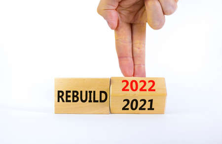 2022 rebuild new year symbol. Businessman turns a wooden cube and changes words 'Rebuild 2021' to 'Rebuild 2022'. Beautiful white background, copy space. Business, 2022 rebuild new year concept.