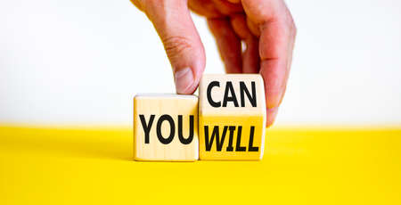 You can and will symbol. Businessman turns a cube and changes words you can to you will. Beautiful white and yellow background, copy space. Business, motivational and you can and will concept.