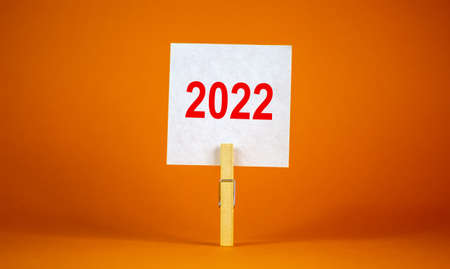 2022 happy new year symbol. Wooden clothespin, white sheet of paper with number 2022. Beautiful orange background, copy space. Business and 2022 happy new year concept.