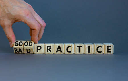 Good or bad practice symbol. Businessman turns wooden cubes and changes words 'bad practice' to 'good practice'. Beautiful gray background. Business, good or bad practice concept. Copy space. 스톡 콘텐츠