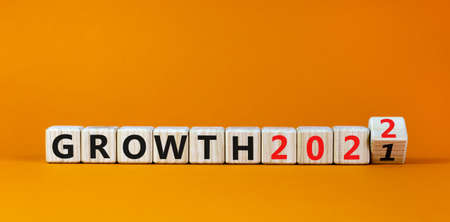 Planning 2022 growth new year symbol. Turned a wooden cube and changed words 'Growth 2021' to 'Growth 2022'. Beautiful orange background, copy space. Business, 2022 growth new year concept.