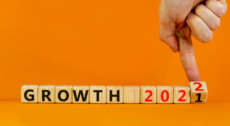 Planning 2022 growth new year symbol. Businessman turns wooden cubes and changes words 'Growth 2021' to 'Growth 2022'. Beautiful orange background, copy space. Business, 2022 growth new year concept. 스톡 콘텐츠