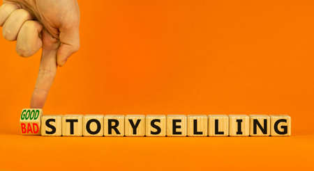 Good or bad storyselling symbol. Businessman turns a wooden cube, changes words 'bad storyselling' to 'good storyselling'. Beautiful orange background, copy space. Business and storytelling concept. 스톡 콘텐츠