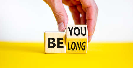 Be you, belong symbol. Businessman hand turns a cube and changes words 'be you' to 'belong'. Beautiful white and yellow background. Business, belonging and be you, belong concept. Copy space. 스톡 콘텐츠