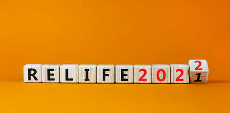 Planning 2022 relife new year symbol. Turned a wooden cube and changed words 'relife 2021' to 'relife 2022'. Beautiful orange background, copy space. Business, 2022 relife new year concept.