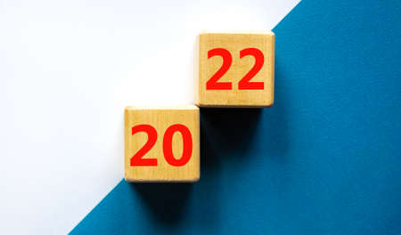 2022 happy new year symbol. Wooden cubes symbolize the change from 2021 to the new year 2022. Beautiful white and blue background. Copy space. Business and 2022 happy new year concept. 스톡 콘텐츠