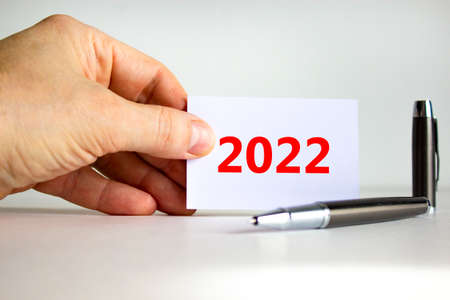 2022 happy new year symbol. Businessman holds white card with number 2022. Metallic pen. Beautiful white background, copy space. Business and 2022 happy new year concept.
