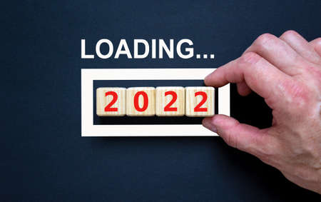 2022 happy new year symbol. Wooden cubes symbolize the change to the new year 2022. Businessman hand, word loading. Beautiful black background. Copy space. Business, 2022 happy new year concept.