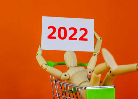2022 happy new year symbol. White sheet of paper with number 2022. Wooden model of a human in a shopping cart. Beautiful orange background, copy space. Business and 2022 happy new year concept. 스톡 콘텐츠