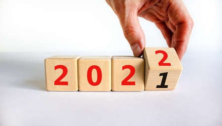 2022 happy new year symbol. Businessman turns a cube, symbolize the change from 2021 to the new year 2022. Beautiful white background. Copy space. Business and 2022 happy new year concept.