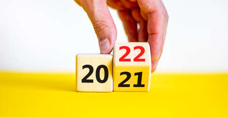2022 happy new year symbol. Businessman turns a cube, symbolize the change from 2021 to the new year 2022. Beautiful yellow and white background. Copy space. Business and 2022 happy new year concept. 스톡 콘텐츠