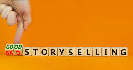 Good or bad storyselling symbol. Businessman turns wooden cubes, changes words 'bad storyselling' to 'good storyselling'. Beautiful orange background, copy space. Business and storytelling concept.