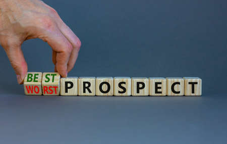Best or worst prospect symbol. Businessman turns wooden cubes and changes words 'worst prospect' to 'best prospect'. Beautiful gray background. Business, best or worst prospect concept. Copy space.