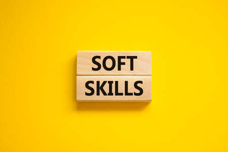 Soft skills symbol. Concept words 'Soft skills' on wooden blocks on a beautiful yellow background. Business, educational and soft skills concept, copy space.