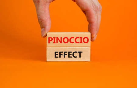 Pinoccio effect symbol. Concept words Pinoccio effect on wooden blocks on a beautiful orange background. Businessman hand. Business and Pinoccio effect concept, copy space. 스톡 콘텐츠