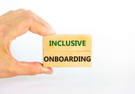 Inclusive onboarding symbol. Wooden blocks with words Inclusive onboarding on beautiful white background. Businessman hand. Business, HR and inclusive onboarding concept. Copy space.