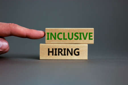 Inclusive hiring symbol. Wooden blocks with words Inclusive hiring on beautiful gray background. Businessman hand. Business, HR and inclusive hiring concept. Copy space. 스톡 콘텐츠