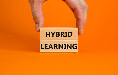 Hybrid learning symbol. Concept words 'Hybrid learning' on wooden blocks on a beautiful orange background. Businessman hand. Business, educational and hybrid learning concept, copy space. 스톡 콘텐츠