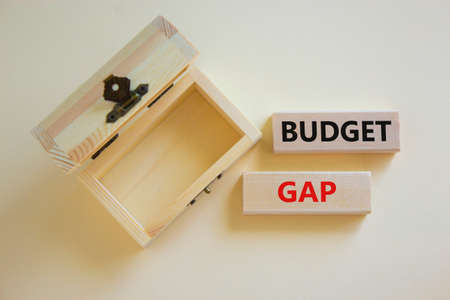 Budget gap symbol. Concept words 'budget gap' on wooden blocks on a beautiful white background, empthy wooden chest. Business and budget gap concept, copy space.