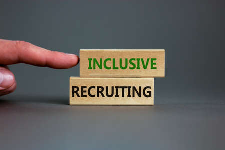 Inclusive recruiting symbol. Wooden blocks with words Inclusive recruiting on beautiful gray background. Businessman hand. Business, HR and inclusive recruiting concept. Copy space.