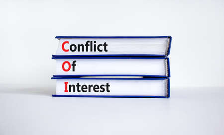 COI, Conflict of interest symbol. Books with concept words 'COI, conflict of interest'. Beautiful white background. Copy space. Business and COI, conflict of interest concept.
