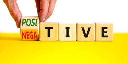 Positive or negative symbol. Businessman turns a wooden cube, changes the word 'negative' to 'positive'. Beautiful yellow table, white background, copy space. Business, positive or negative concept.