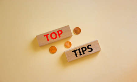 Top tips symbol. Concept words 'top tips' on wooden blocks on a beautiful white background, metallic coins. Business and top tips concept, copy space.