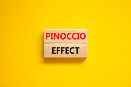 Pinoccio effect symbol. Concept words Pinoccio effect on wooden blocks on a beautiful yellow background. Business and Pinoccio effect concept, copy space.