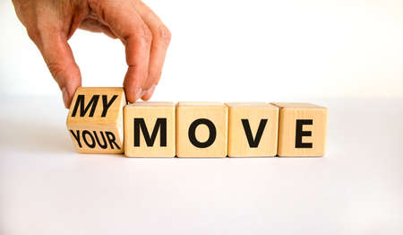My or your move symbol. Businessman turns a wooden cube and changes words 'your move' to 'my move'. Beautiful white table, white background. My or your move and business concept. Copy space.