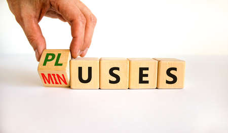 Pluses and minuses symbol. Businessman turns a wooden cube and changes the word 'minuses' to 'pluses'. Beautiful white table, white background. Business, pluses and minuses concept, copy space. 스톡 콘텐츠