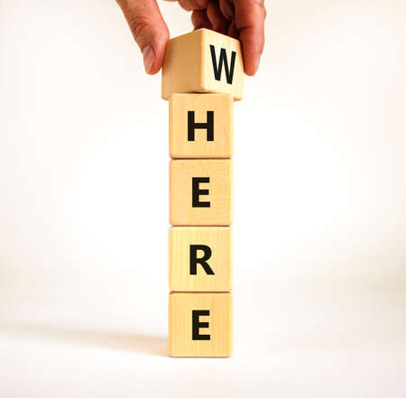 Where or here symbol. Businessman turns a wooden cube, changes the word 'where' to 'here'. Beautiful white table, white background, copy space. Business, where or here concept. 스톡 콘텐츠