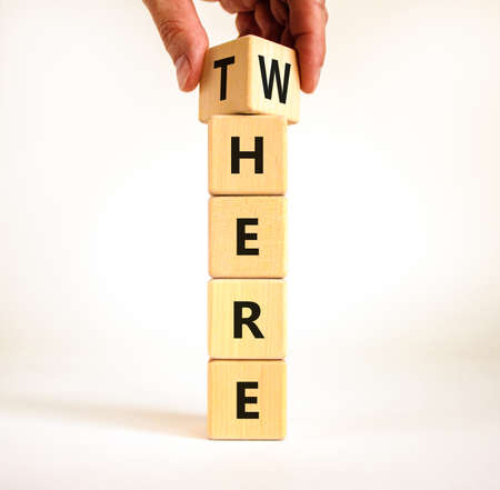 There or where symbol. Businessman turns a wooden cube, changes the word 'there' to 'where'. Beautiful white table, white background, copy space. Business, there or where concept.
