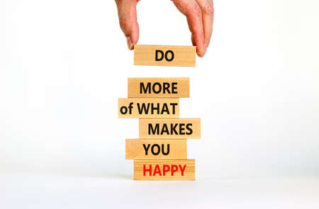 Do what makes you happy symbol. Wooden blocks with words 'Do more of what makes you happy'. Businessman hand. Beautiful white background, copy space. Business, do what makes you happy concept.