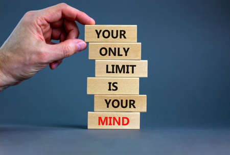 Your only limit is your mind symbol. Wooden blocks with words 'Your only limit is your mind'. Businessman hand. Beautiful gray background. Business, popular quotation concept. Copy space.